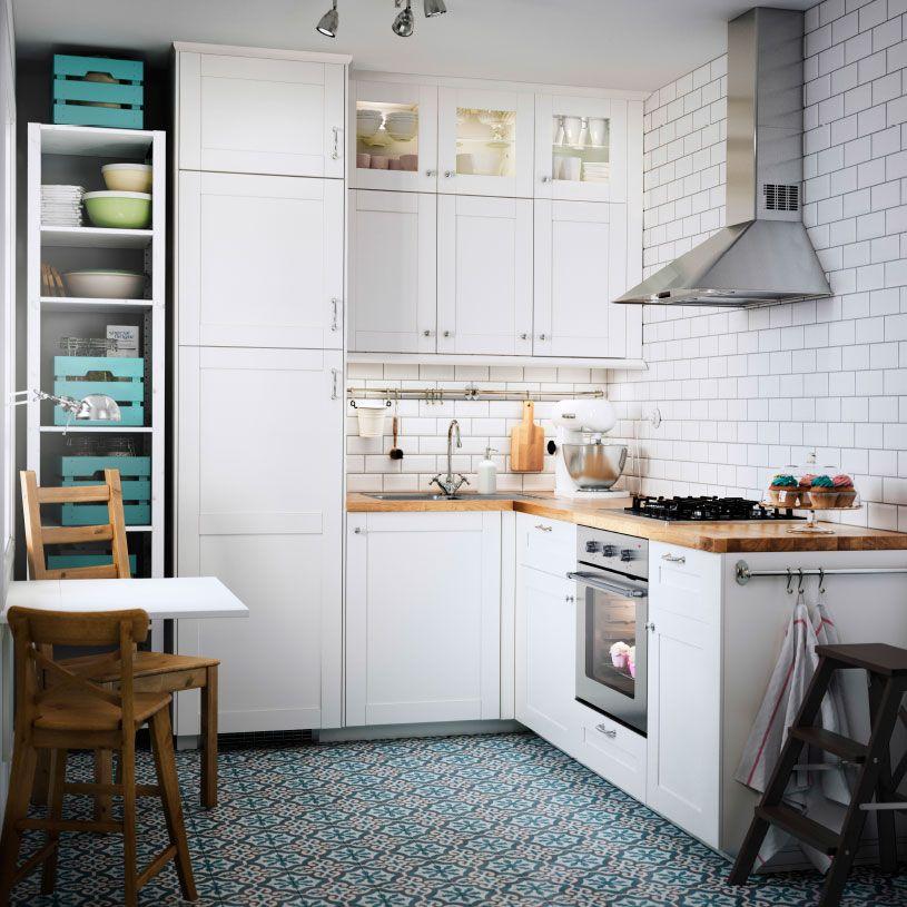 Pieni valkoinen keittiö, jossa tamminen työtaso ja rosterinen uuni ja liesituuletin.