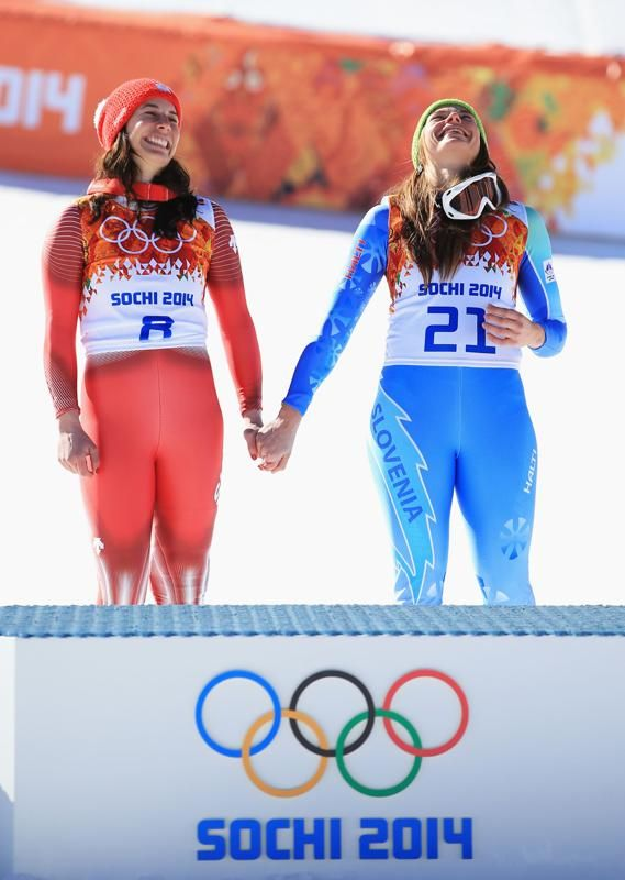 Gold medalists Dominique Gisin of Switzerland  and Tina Maze of Slovenia hold hands during the flower ceremony for during the Alpine Skiing Women's Downhill on day 5 of the Sochi 2014 Winter Olympics at Rosa Khutor Alpine Center on February 12, 2014 in Sochi, Russia.