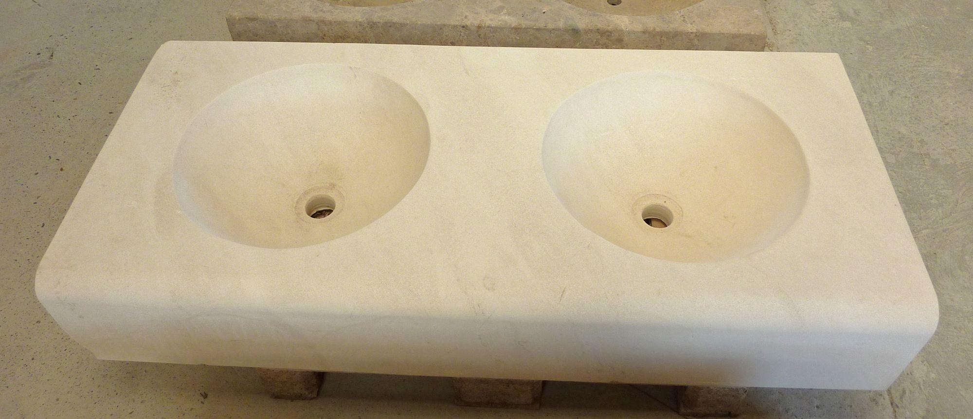 Un élégant évier taillé dans la pierre naturelle blanche du Gard. Il possède deux bacs incurvés et est doté de beaux et larges rebords qui peuvent servir à déposer tout votre nécessaire de toilette.