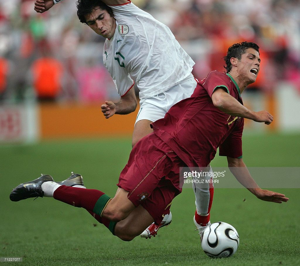 Portuguese forward Cristiano Ronaldo (R) goes airborne challenged by Iranian midfielder Mehrzad Madanchi (L) during the World Cup 2006 group D football game Portugual vs.Iran 17 June 2006 at Frankfurt stadium.