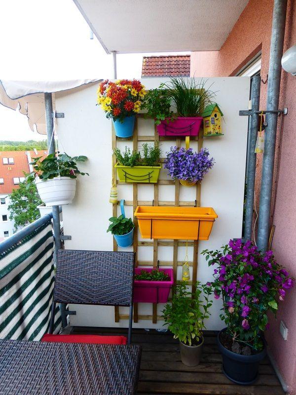 Photo of Vertical Balcony Garden Idea – An dieser Holzhalterung hängen bunte Pflanzgefäße …