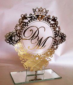 Topo de bolo em metal, banhado a ouro, modelo brasão com monograma dos noivos.