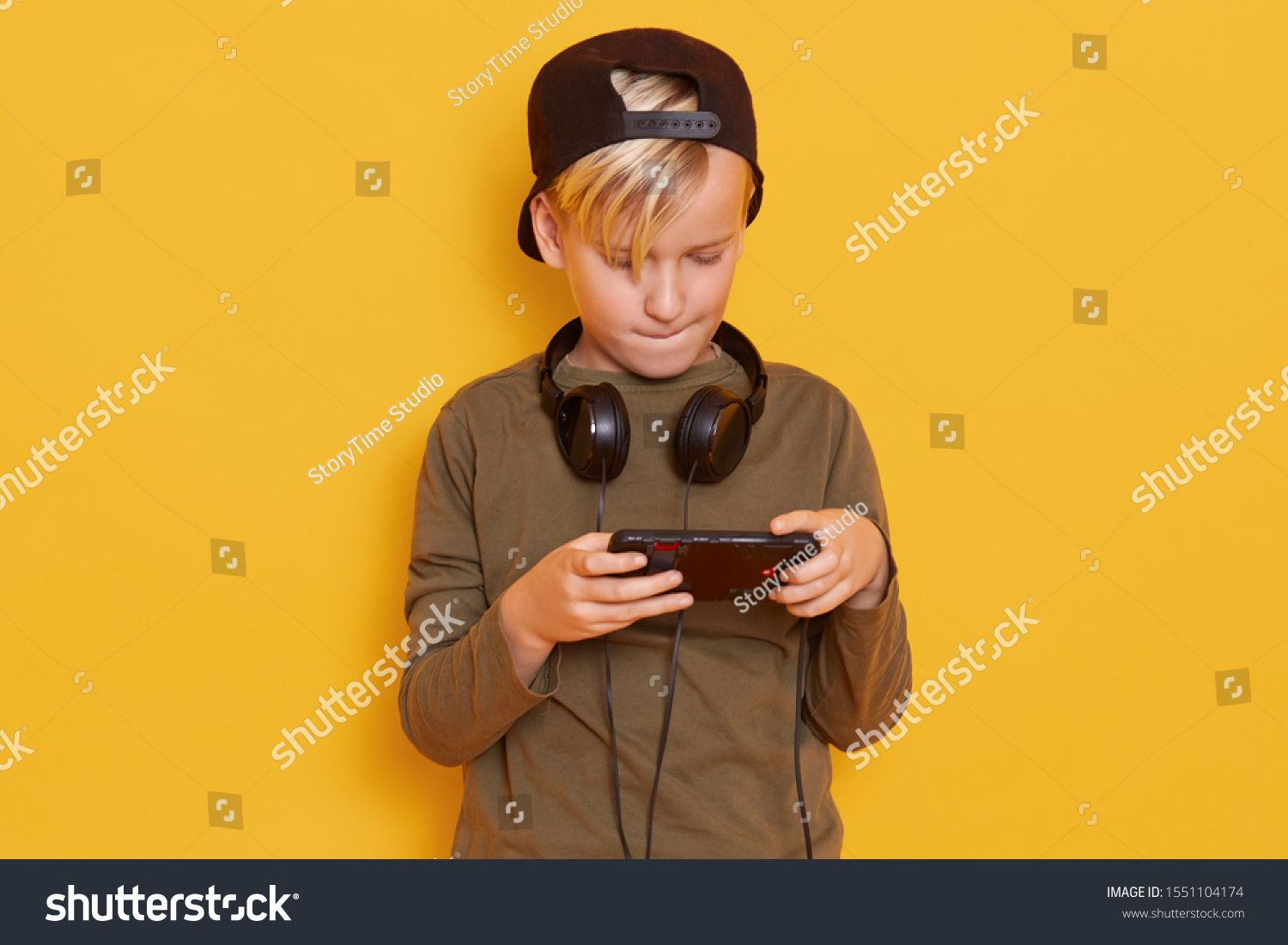 Close up portrait of little boy using mobile phone, child playing on smartphone and biting his lower lip, posing isolated over yellow studio background. Technology, mobile apps, children concept. #Ad , #Aff, #playing#child#biting#smartphone #lipsbackground