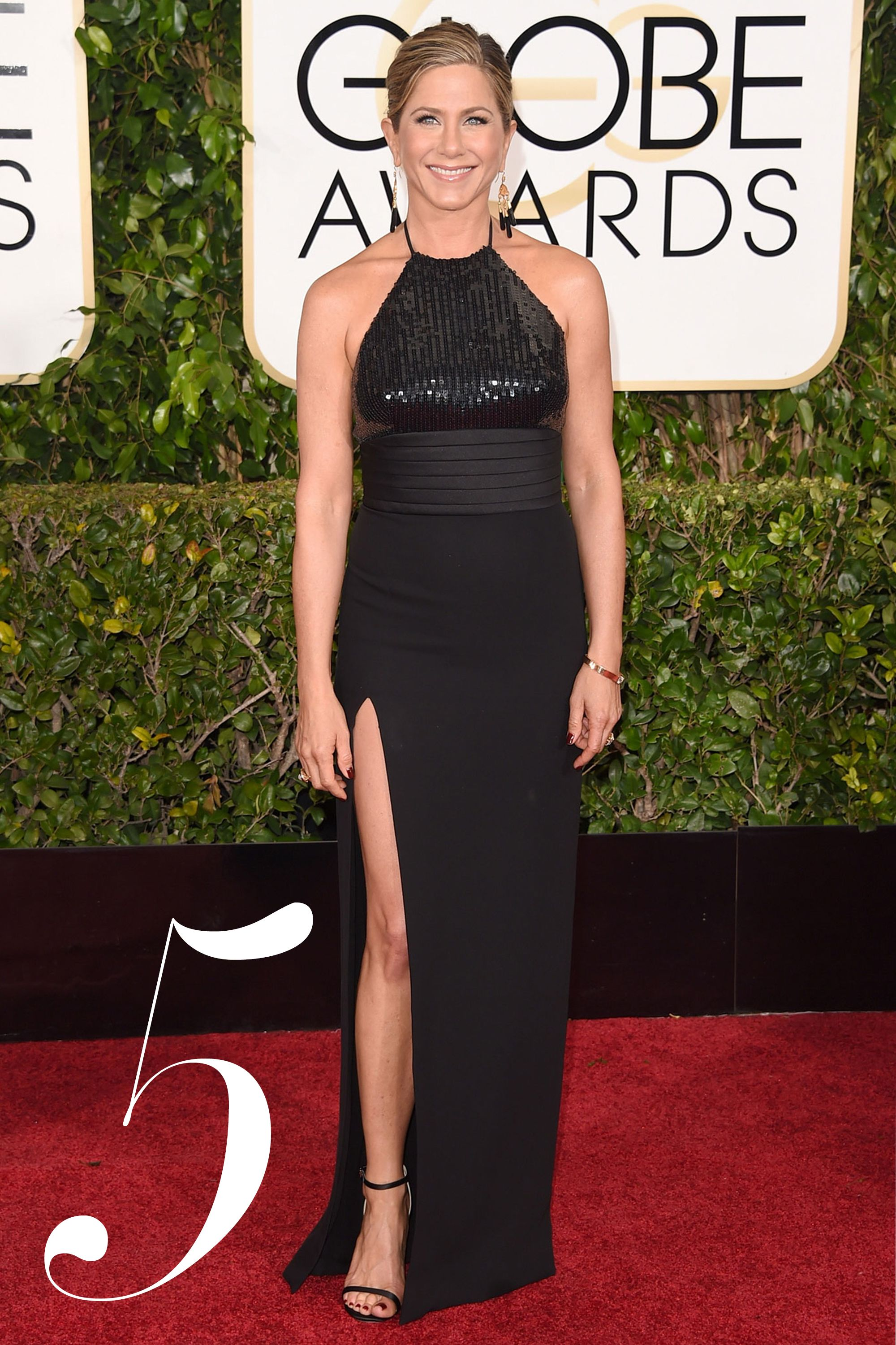 2015 Golden Globes - Jennifer Aniston in Saint Laurent may be black, but the '90s-style slit and halter neck are a nod of what's to come. Getty  - HarpersBAZAAR.com