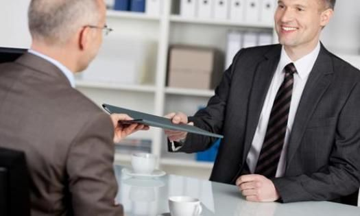 A job seeker hands a hiring manager his resume during a second