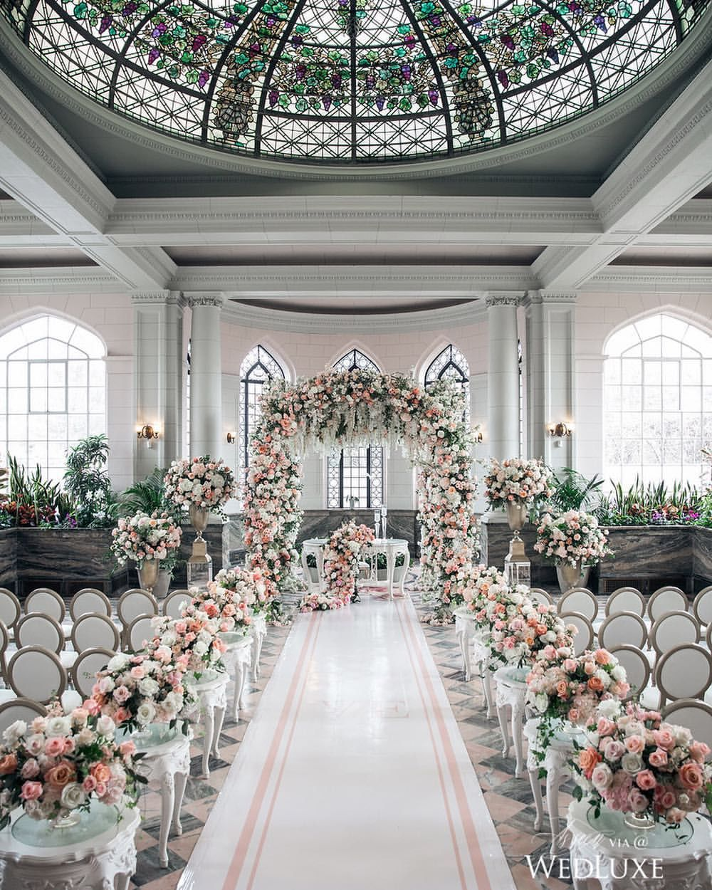 Dreamy floral arch ✔️Stained glass ceiling ✔️Custom aisle runner ✔️Could this wedding be more perfect?