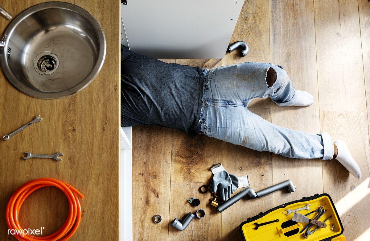 Download premium photo of Plumber man fixing kitchen sink