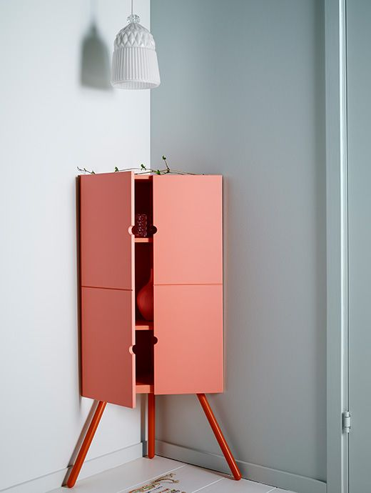 Pink Wooden IKEA Corner Cabinet With A White Glass Lampshade Hanging Above It