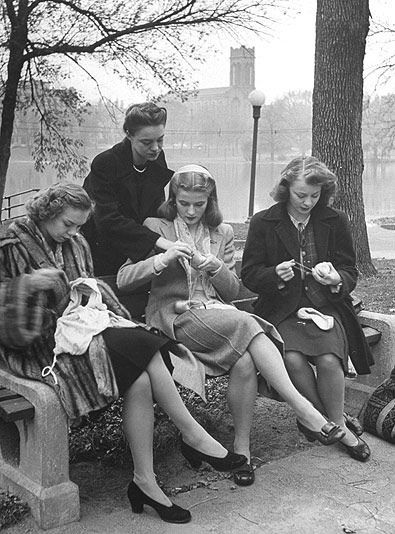 Several girls knitting in the 1940s.  It looks as if the lady standing it teaching the ones who are sitting down...