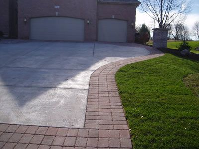 A Triple Course Of Edging Around This Concrete Driveway Complements The  Brick House.