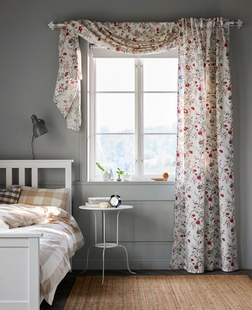 A floralprinted curtain hangs in a window in a bedroom