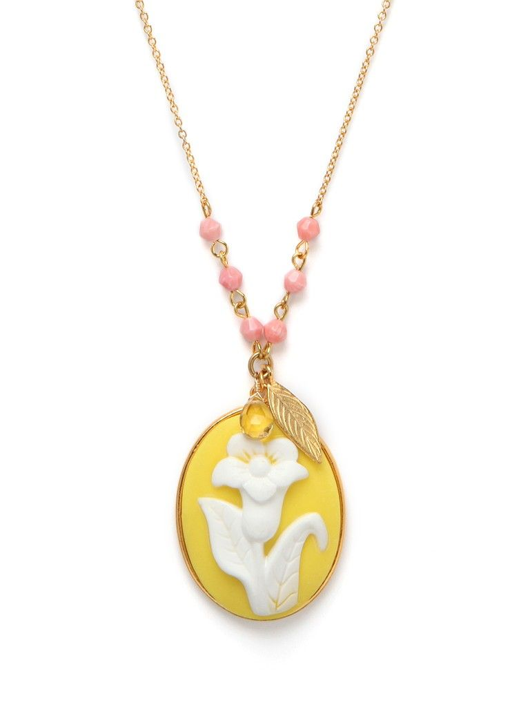 This beautiful carved cameo, cast in sunny yellow and featuring a pretty petunia flower, recalls all the romantic glamour of the Victorian era, right down to the delicate chains, beads and gold leaf accents.