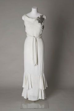 1935 wedding dress: Worn by Blanche Annette Rosenberg (1913-1992) for her wedding to Gerald Pearlman (1912-1986), at Princes Road Synagogue, Liverpool, on 14 August 1935. The groom was a jeweller and the couple's families both came from Russia to settle in Britain in the 1900s. The Synagogue in Princes Road was designed and decorated by Liverpool architects W & G Audsley and is considered one of the most magnificent in Britain.