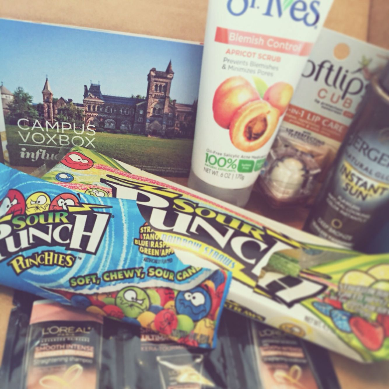 #CampusVoxBox contents! Jergens Natural Glow Instant Sun Sunless Tanning Mousse, St. Ives Blemish Control Apricot Scrub, L'Oreal Paris Asvanced Straight System, Softlips Cube, Sour Punch Rainbow Straws, and Sour Punch Punchies