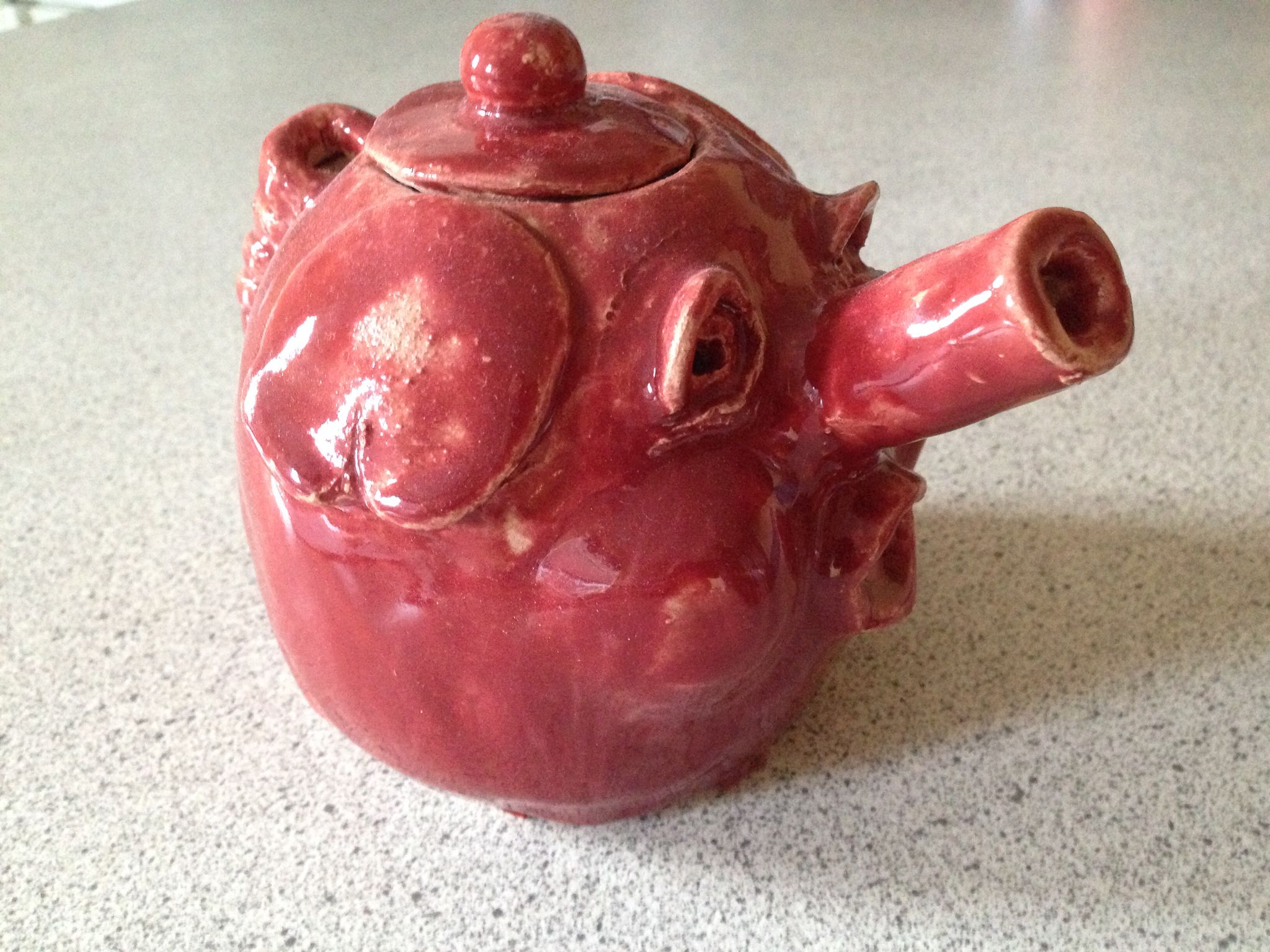 Percy pig pink teapot. Made from grey grey clay from joined pinch pots. Functional with a curly pigs tail handle and a slab built spout!