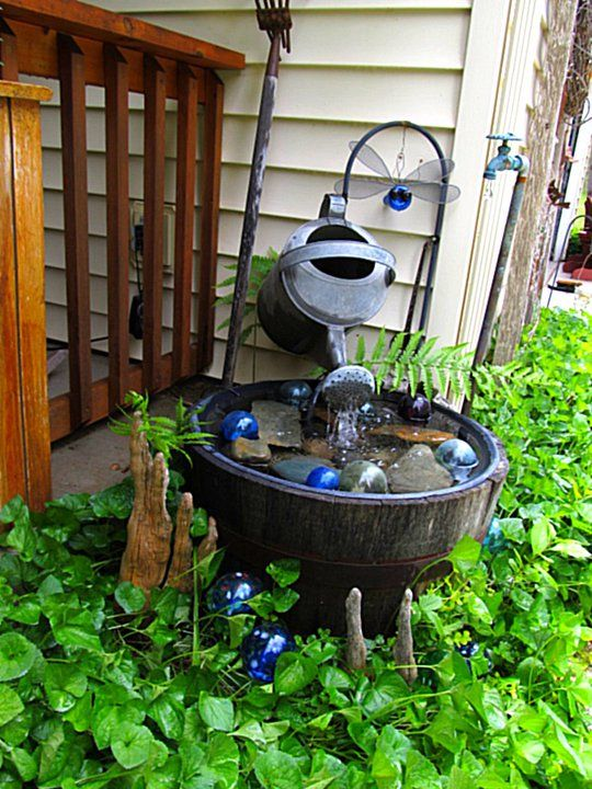 """Flea Market Gardening fountain: """"I placed a small rustic board across the back of the top of the barrel and attached the pump to that.  I drilled a hole in the board and threaded the tubing through that and an old watering can, added some glass floats,"""" says Kirk Willis"""
