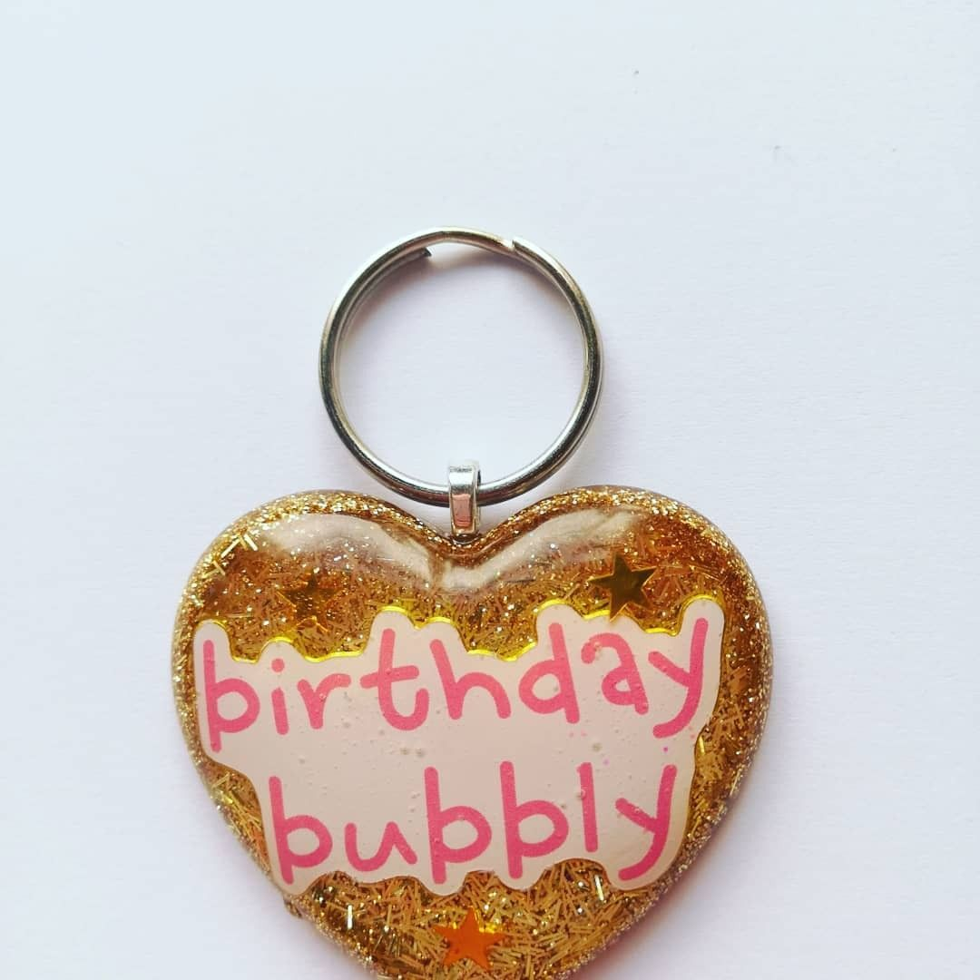 Birthday Heart Resin Keyring #goldglitterbackground Birthday Bubbly Foil Sticker with Shiny Gold Star Decor with a Gold Glitter Background, attached to a Silver Heart Shaped Glue-On Bail with a Standard Silver Circle Split Ring #goldglitterbackground