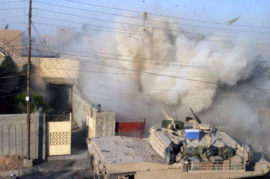 An U.S. Marine Corps M1A1 Abrams tank fires its main gun into a building to provide suppressive fire against insurgents who fired on other U.S. Marines during a firefight in Fallujah, Al Anbar province, Iraq, Dec. 10, 2004. U.S. Marine Corps photo