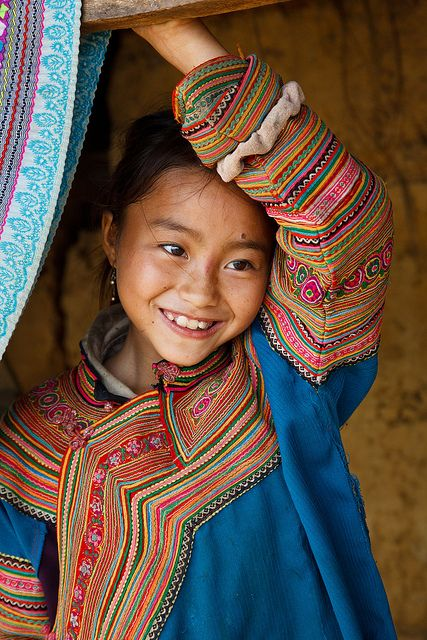 Portrait of a Flower H'mong hill tribe girl wearing traditionally colourful clothing, in a small village between Coc Ly and Cao Son.  Copyright © Kimberley Coole