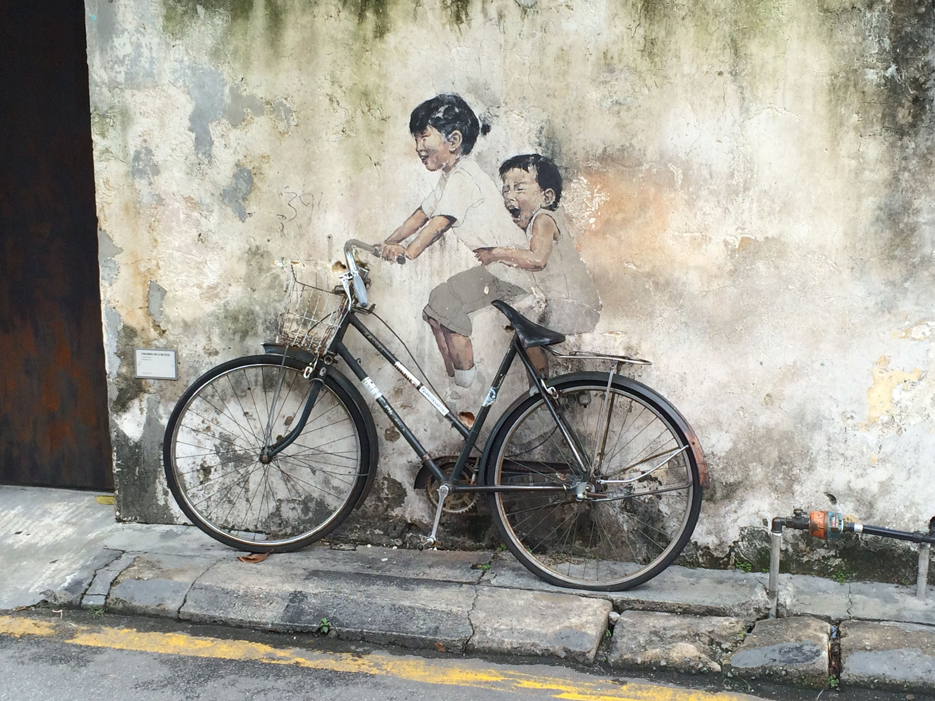 The most iconic penang street art two kids enjoying a bicycle ride