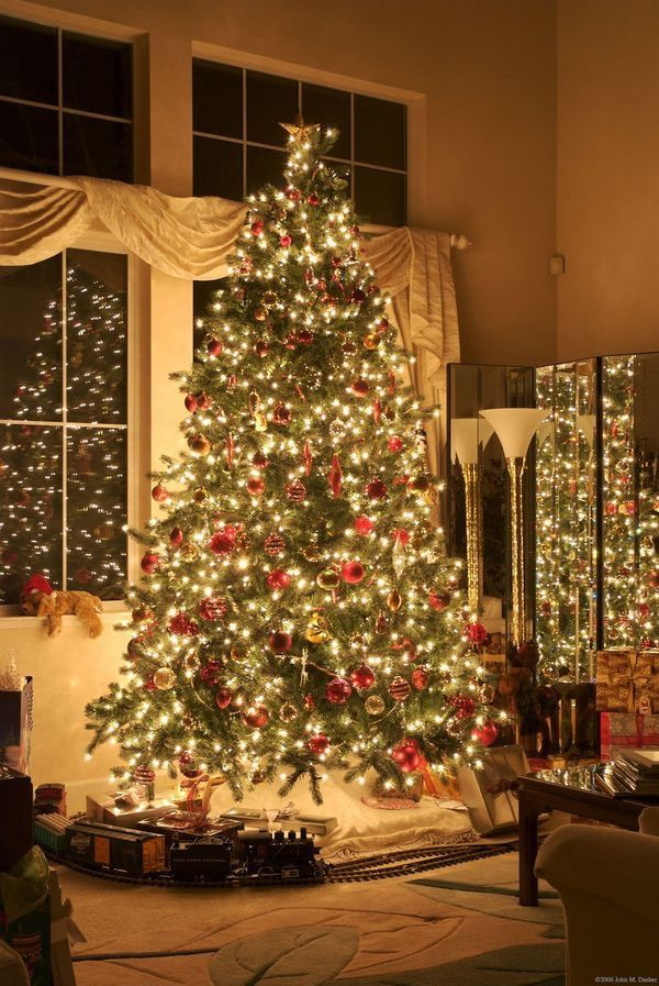 Christmas Tree with train and tracks set up at base, along with a few presents ~ love the whole look!