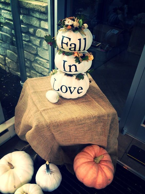 a stack of white pumpkins decorated with blooms, foliage and letters as a fall bridal shower