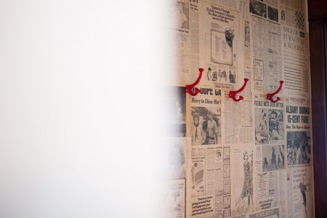 Vintage newsprint as wallpaper.  I love the splash with the red hooks.    Nadia Geller Designs » farm/san diego