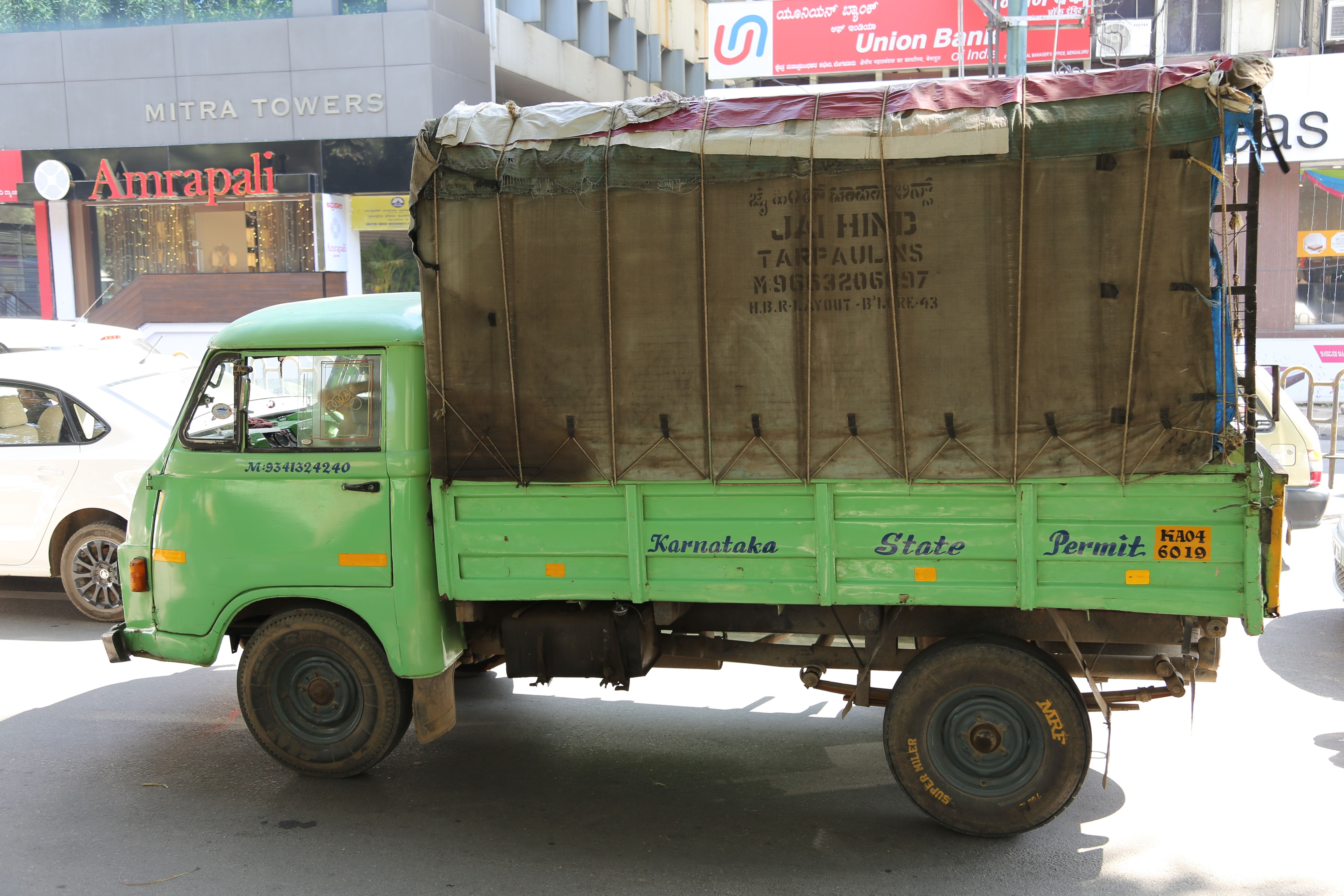 Green And Brown Drop Side Truck Near Gray Building Cars Demolition Service Flood Damage Trucks