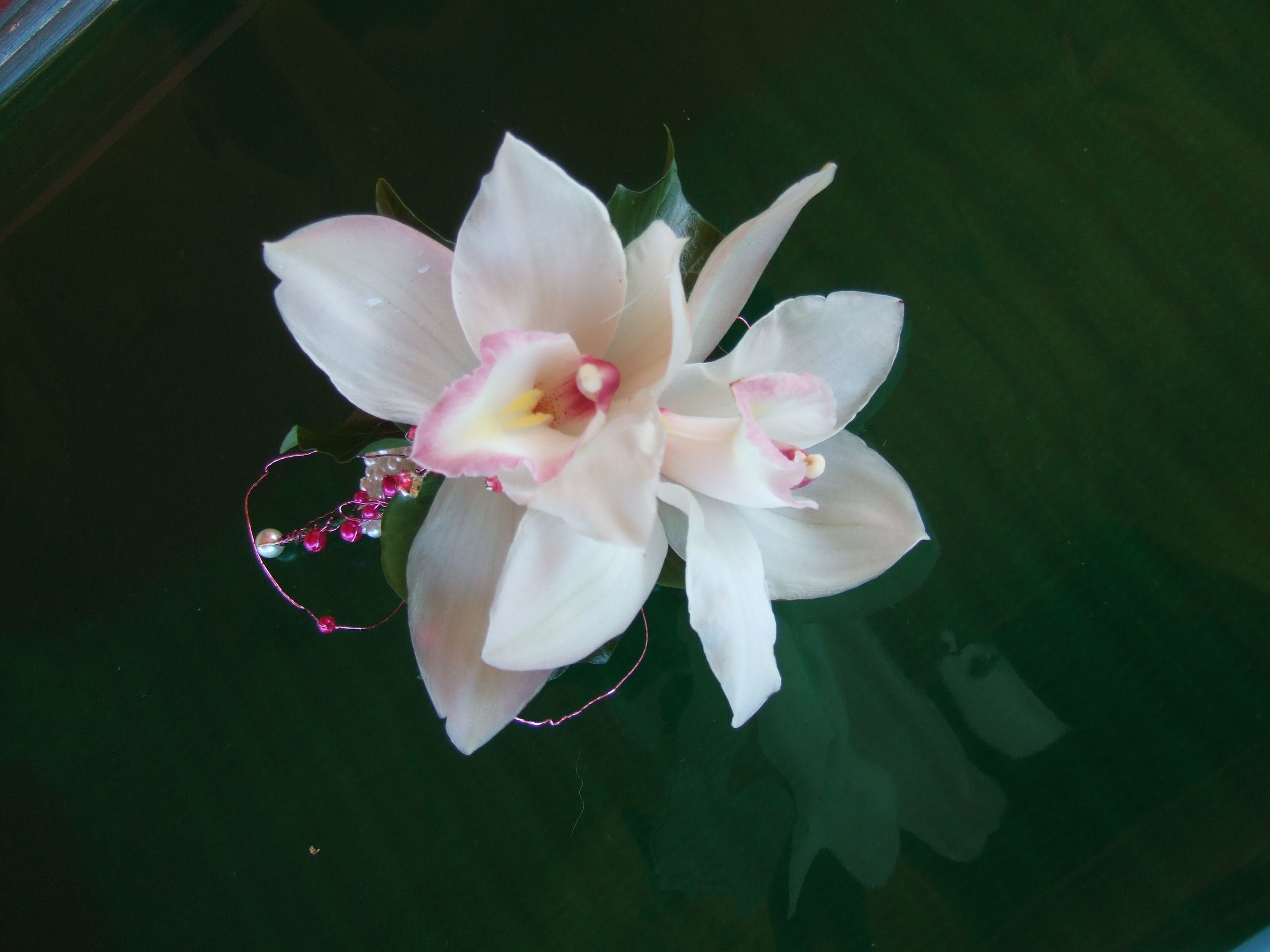 Beautiful white and pink cymbidium orchid wrist corsage finished off with pink wire work and pearl beads.