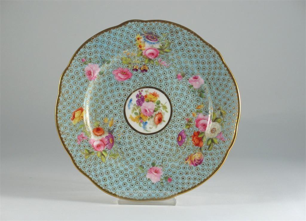 A fine Nantgarw plate, painted with colourful flowers, on a pale eau-de-Nile and gilt oeil-de-perdrix, impressed 'Nantgarw CW' mark, c.1817-20, 21cm. Cf. W.D. John, Nantgarw Porcelain Album, illus.66.