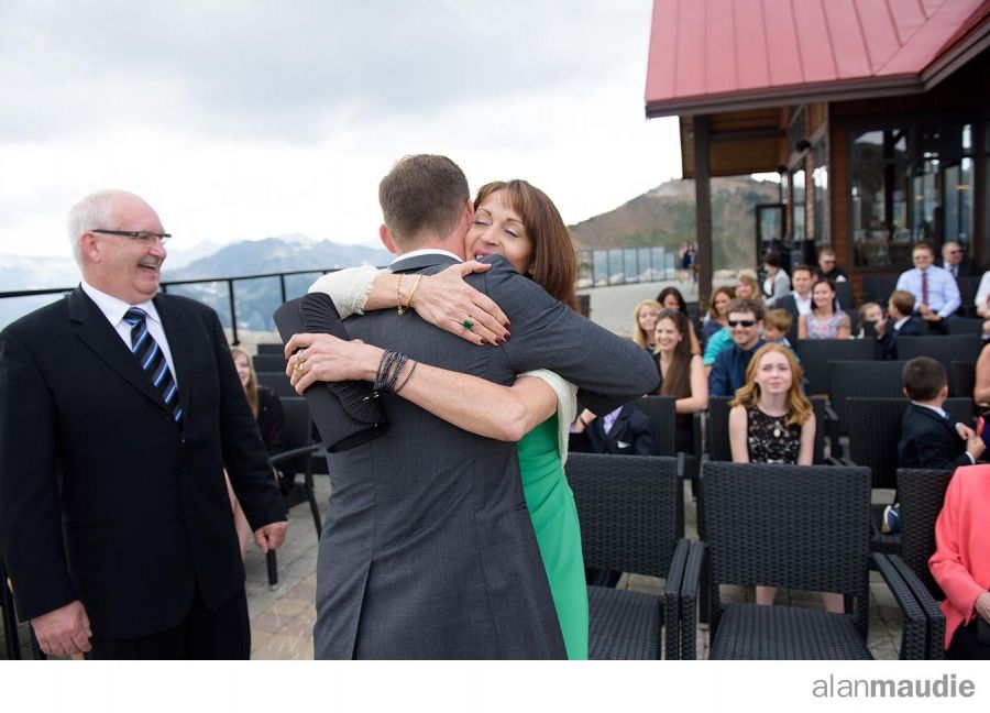 Mom hugs groom on mountaintop, Kicking Horse Mountain Resort Wedding Photographer, Golden. B.C., BC