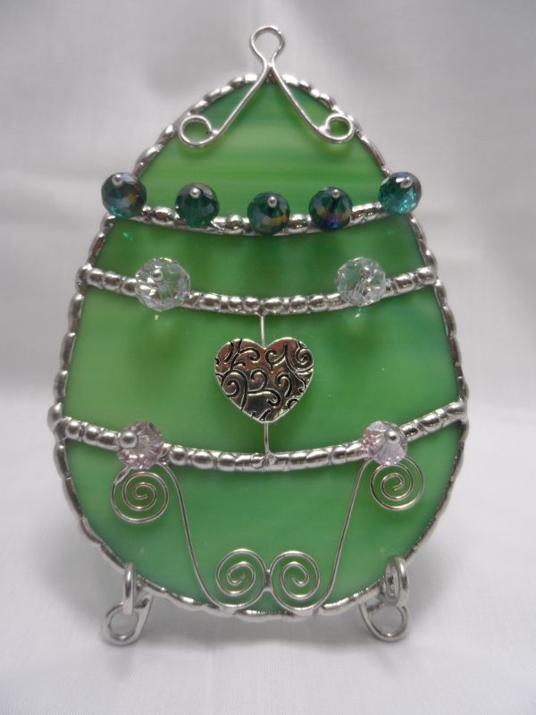 """Stained Glass Easter Egg in Green with Green Cut Glass and a Heart, sort of a retro / vintage style. Egg is 4"""" high and 3"""" wide. Comes with tripod wire stand or hanging chain. At Jitter Beans in Mineral Wells, Texas"""