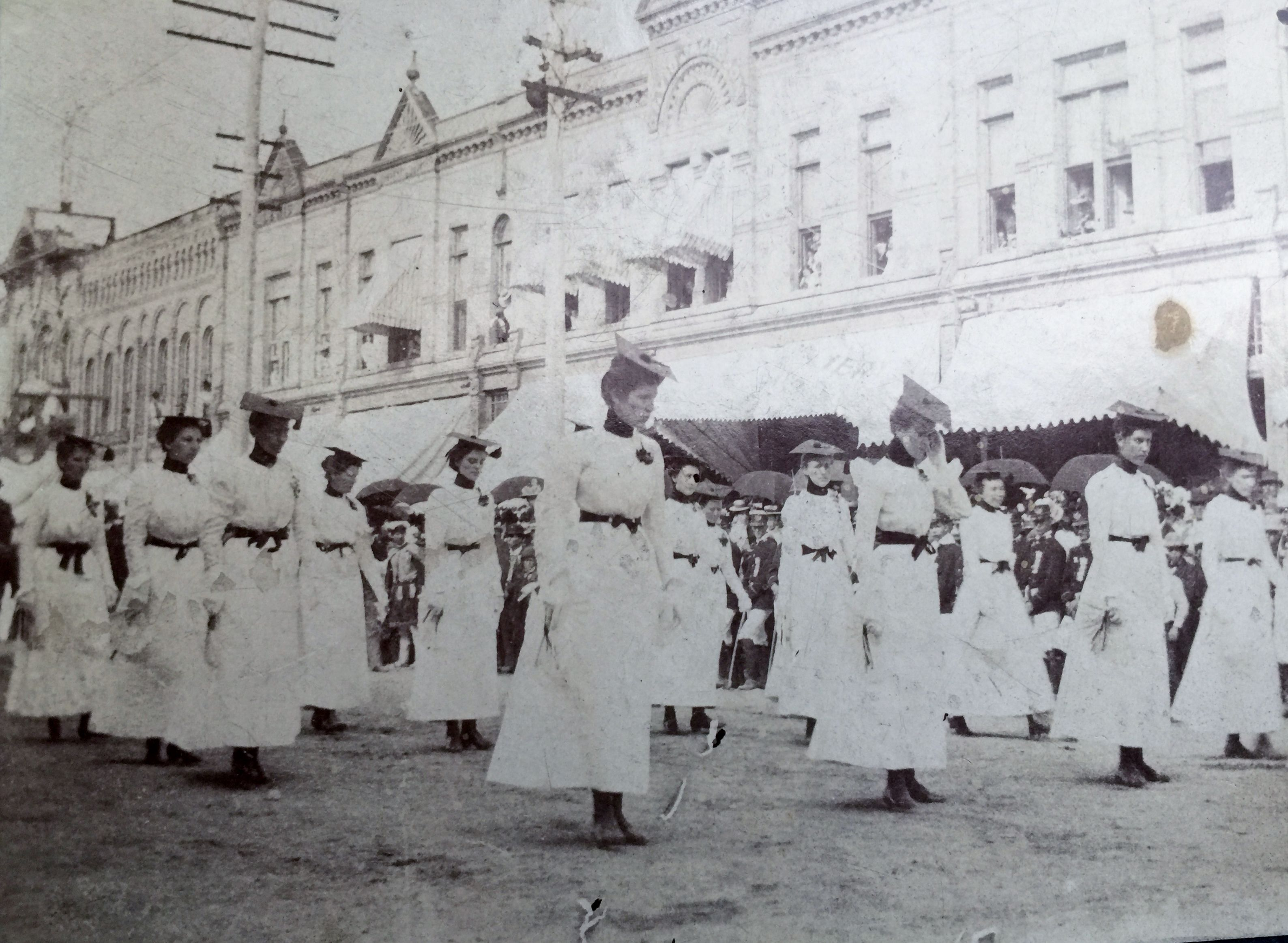 Ladies of the Maccabees march down Lafayette Street, Greenville, Michigan. Circa 1880.