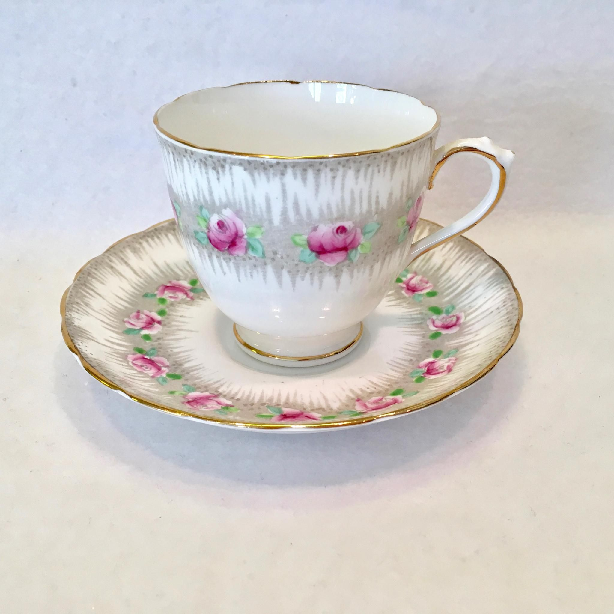 This pretty Plant Tuscan Bone China Teacup and Saucer with enameled Pink Roses and Green Leaves on Gray is numbered C6561. A ring of pretty pink rose