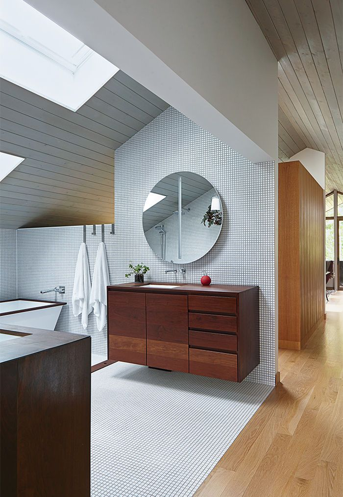 i love the large round mirror in this kansas city master bathroom with walnut vanity and