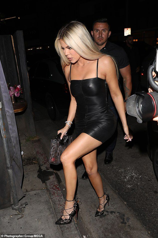 Khloe Kardashian displays her hourglass curves in a leather LBD