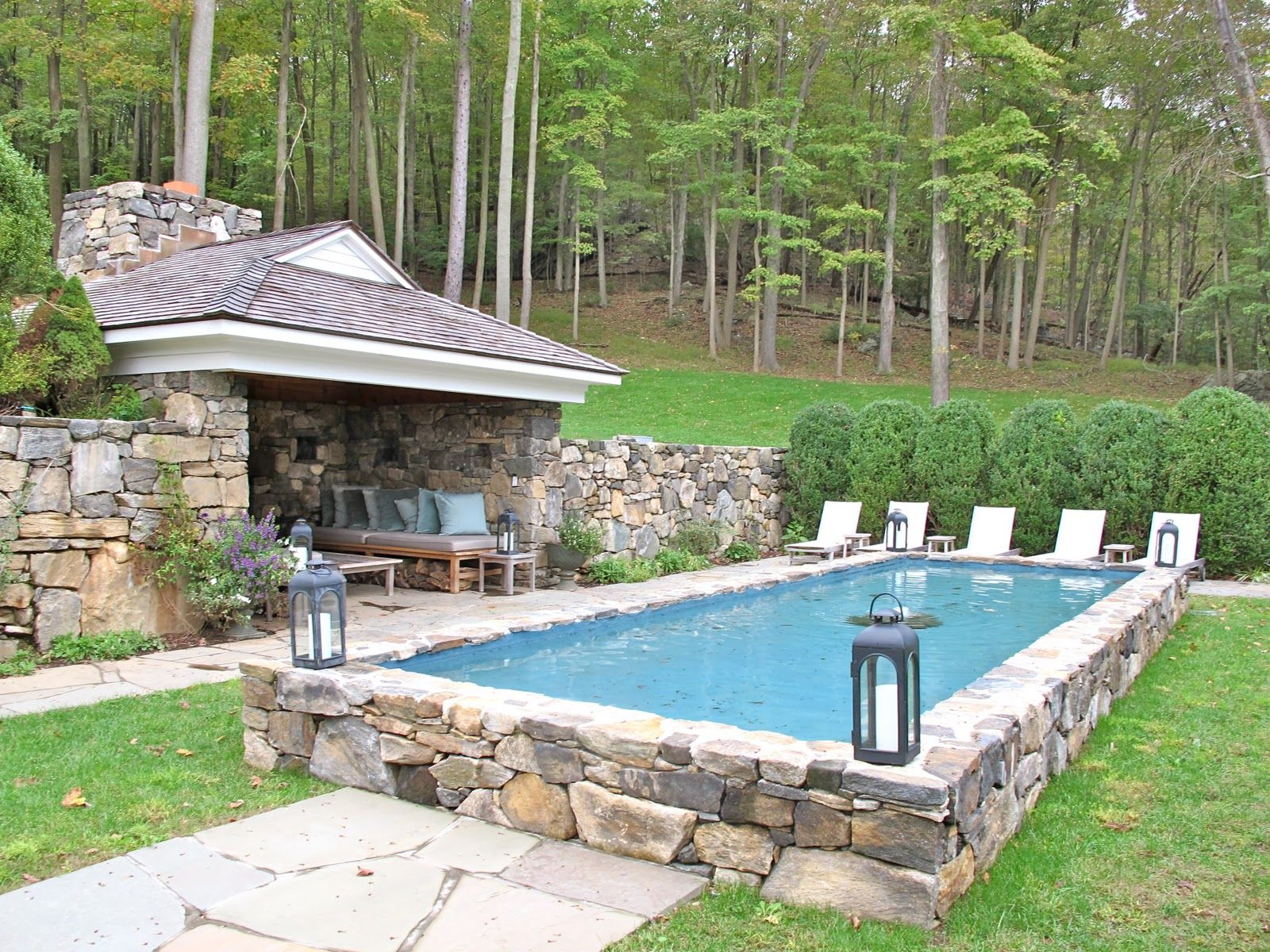Semi inground pool surrounded by stone pool splashpad for On ground pools