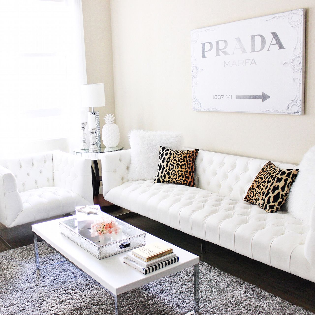 Awesome Blondie In The City Home Decor | White Tufted Couch | Leopard Pillows |  Prada Canvas