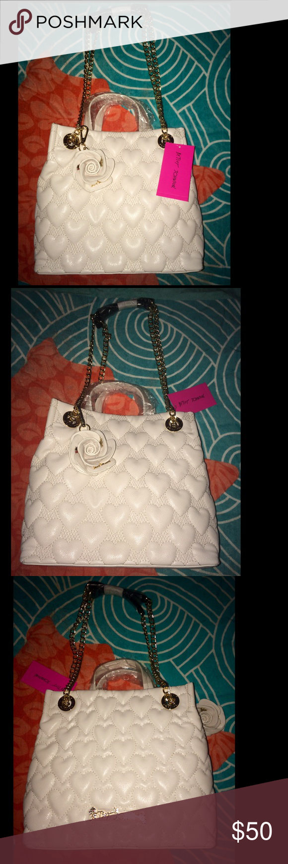 """*New* Betsey Johnson Shopper Bag, White Betsey Johnson """"Bee Mine"""" Heart-Quilted Shopper Bag, in white. This bag has golden hardware and a chain shoulder strap with a hanging floral charm, which has a mirror on one side that says """"Hey, good looking!"""". The shoulder strap has an 11"""" drop. The bag has an open top with a snap-tab closure. Measurements are: 9.8""""H x 11""""W x 5.5""""D; weighs 1 lb. 14.8 oz. Betsey Johnson Bags Shoulder Bags"""