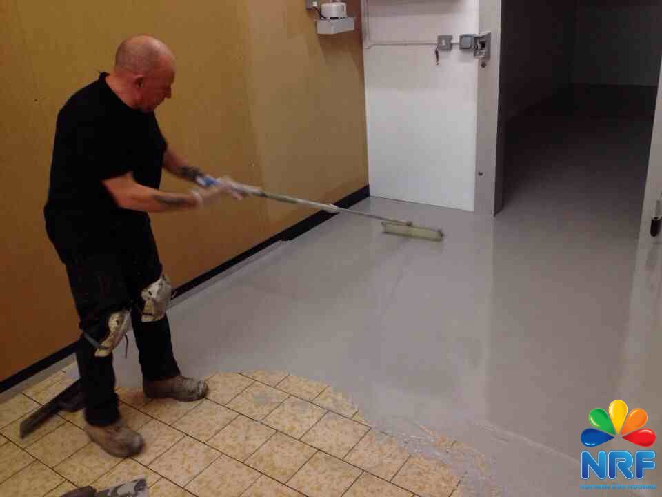 Northern Resin Flooring laying the Polyurethane at Iceland Manchester with Logo.