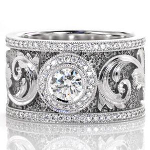 Design 3025 - An elegant motif drapes across this signature band. A 0.50 carat bezel set center is accented with a micro pavé halo. The scroll work along the band is magnificent with hand engraved detail and faceted stipple background that captures the light. Two rows of milgrained micro pavé diamonds frame the design.