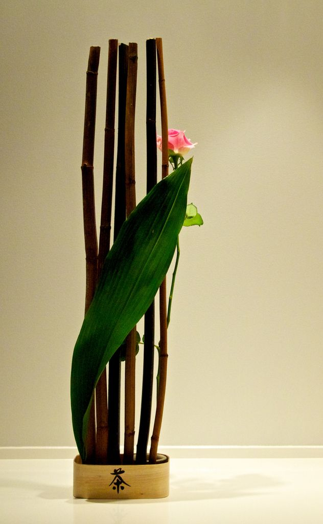 """Valentine's day ikebana: """"A secret sign"""". Dried bamboo - some black painted, pink rose and Aspidistra leaf, in a wooden box with a sign.Lennart Persson"""