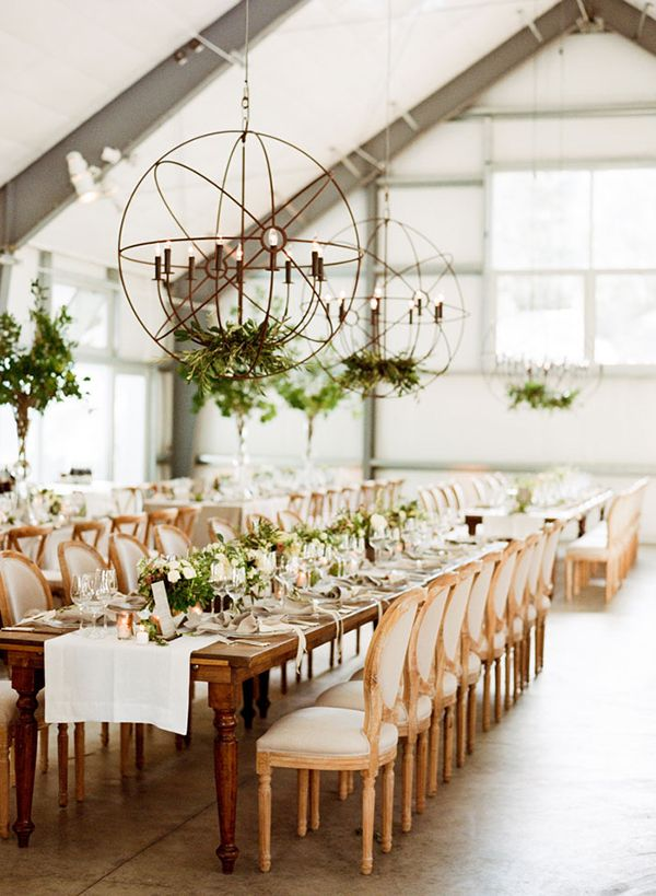 Elegant Barn Reception with Lighting Fixtures adorned with Greenery | Sylvie Gil Photography | http://heyweddinglady.com/rustic-industrial-wedding-inspired-fixer-upper-hgtv/