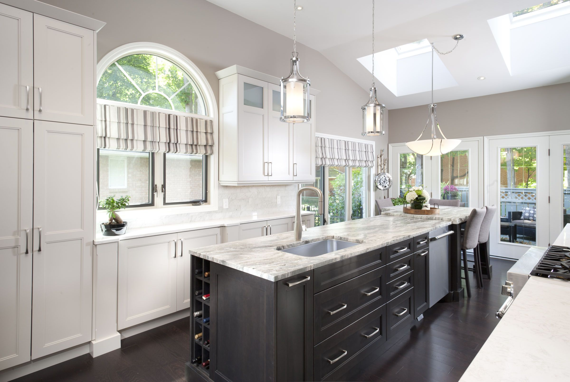Painted white perimeter cabinetry with dark island. Leathered ...
