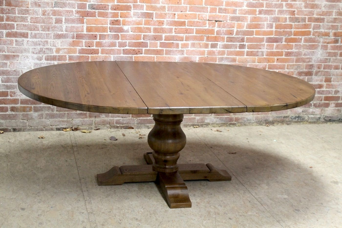 Round farm table made from reclaimed chestnut. Custom made as an extension table with a tuscany pedestal base, all hand crafted.
