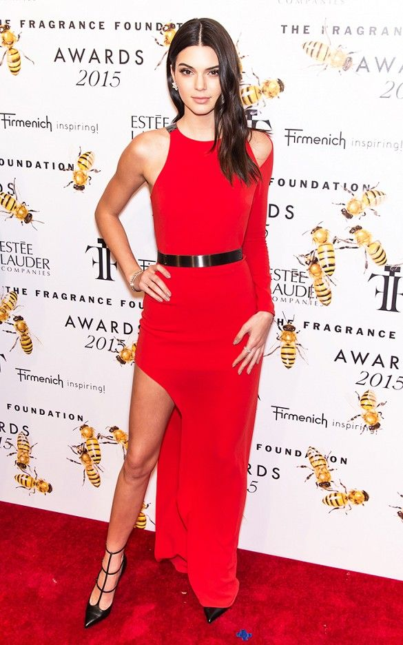 Kendall Jenner wears a red belted dress with a shoulder cutout and high slit with strappy pumps