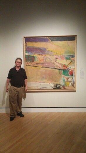 Artist Don Watson standing next to a Richard Diebenkorn painting at Crystal Bridges Museum of art in Arkansas.