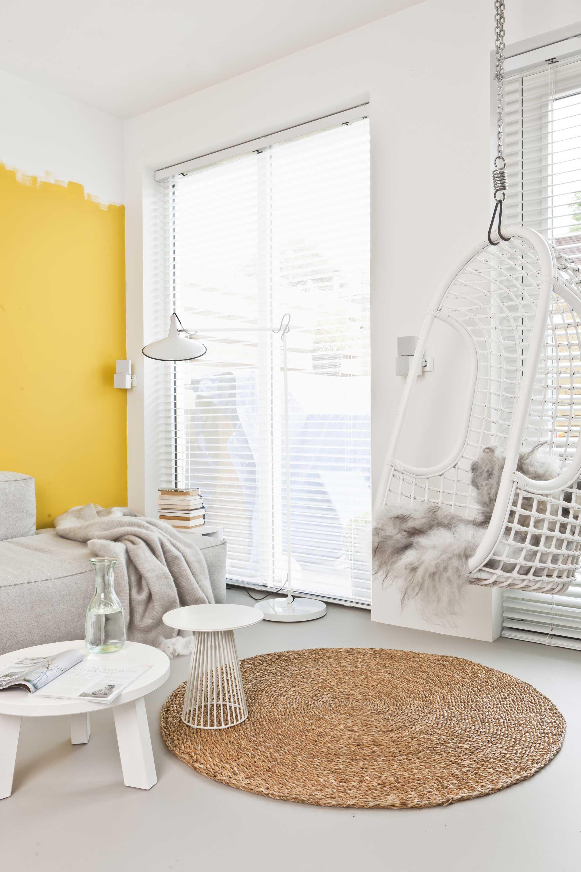 Scandinavische woonkamer met witte hangstoel en gele muur ...