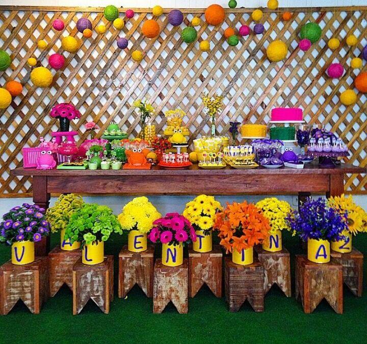 Decoração pra mesa do bolo com o nome da aniversariante em vasos de flores.
