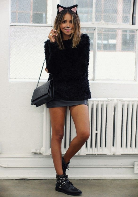 julie sarinana dresses as cool kitty in a black sweater black leather skirt and studded boots